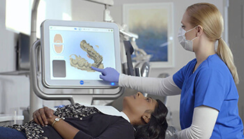 assistant pointing to dental scan