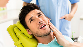 attractive man holding jaw in pain