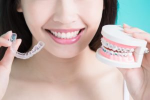 Woman holding clear aligner and braces