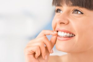 woman smiling inserting Invisalign trays