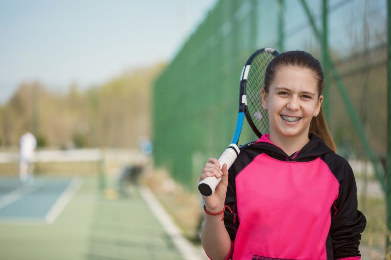 a young girl with braces playing tennis