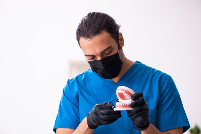 Orthodontist wearing mask and working on model teeth