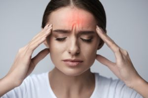 Frowning woman with headache related to her TMJ