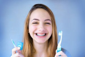 Teen girl holding tools for brushing and flossing with braces