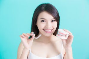 Woman holding Invisalign aligner and dental model with braces