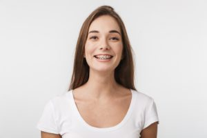 Woman smiling after appointment to repair broken braces